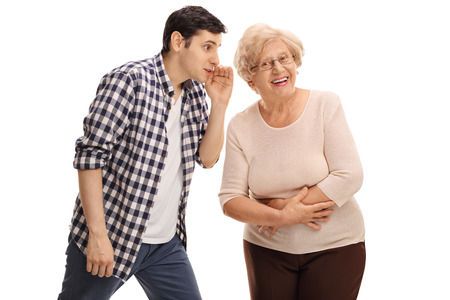 Young guy whispering something to his grandma isolated on white background Stock Photo