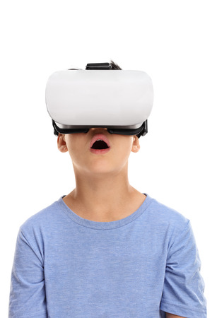 visualizing: Vertical shot of an amazed little kid using a virtual reality goggles isolated on white background Stock Photo