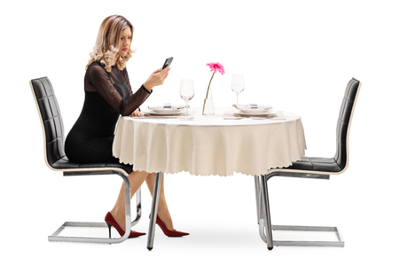 stood up: Young woman reading a text message seated at a restaurant table isolated on white background Stock Photo
