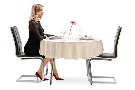 late 20s: Studio shot of a young woman sitting alone at a restaurant table and waiting for her date isolated on white background