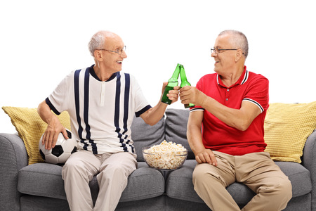 two men: Two senior friends watching a game of football and drinking beer isolated on white background Stock Photo