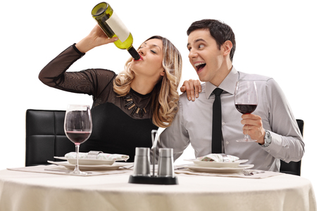 inappropriate: Couple drinking wine directly from the bottle seated on a date isolated on white background