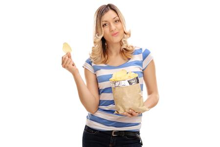 흰 배경에 고립 감자 칩을 먹고 즐거운 젊은 여자