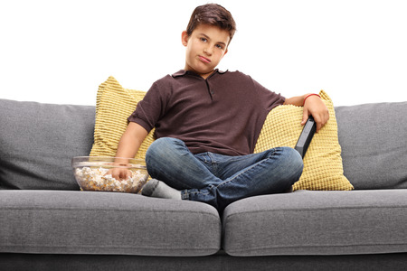 Bored little boy watching TV and eating popcorn seated on a gray sofa isolated on white background Stock Photo