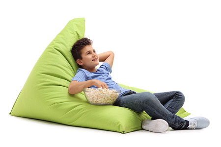 beanbag: Pensive little boy eating popcorn seated on a green beanbag isolated on white background