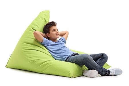 Relaxed jongen die op een comfortabele groene zitzak op een witte achtergrond