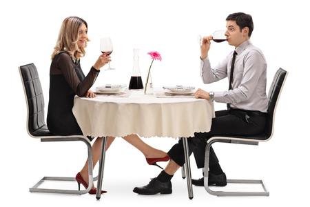 parejas sensuales: Mujer joven que toca un hombre debajo de la mesa con el pie aislado en fondo blanco