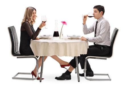 seducing: Young woman touching a man under the table with her foot isolated on white background Stock Photo