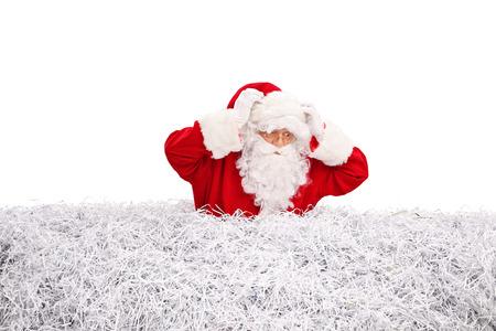 confundido: Confundida Santa Claus en busca de algo en una pila de papel triturado aislado en el fondo blanco