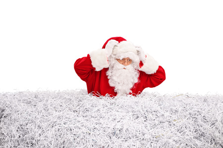 pile of paper: Confused Santa Claus searching for something in a pile of shredded paper isolated on white background