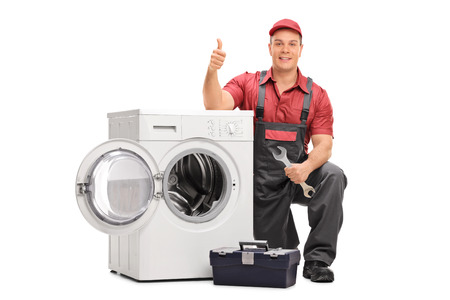 Worker repairing broken washing machine and giving thumb up isolated on white background Reklamní fotografie