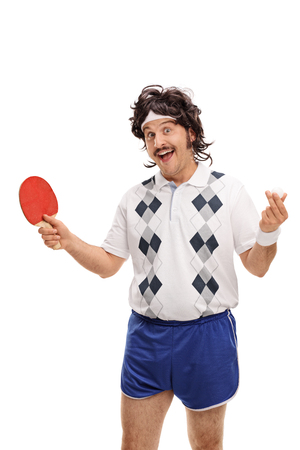 70s tennis: Vertical shot of a retro guy holding a table tennis bat and a ball isolated on white background