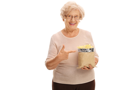 senior woman: Senior woman holding a bag of potato chips and pointing to it with her finger isolated on white background