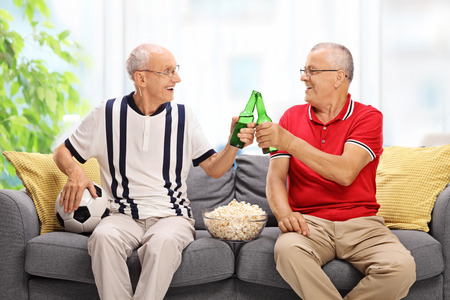 two men: Two elderly men watching a game of football and drinking beer at home