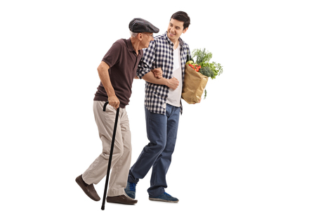 Kind young man helping a senior gentleman with his groceries isolated on white background