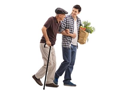 Mit freundlichen jungen Mann einen älteren Herrn mit seiner Lebensmittel isoliert auf weißem Hintergrund zu helfen