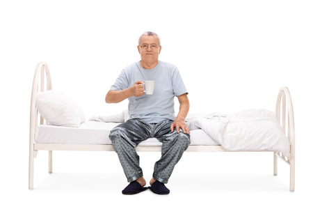 early 60s: Cheerful senior sitting on his bed and holding a cup of coffee isolated on white background