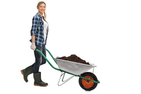 Ritratto integrale di una giovane donna che spinge una carriola piena di sporcizia isolato su sfondo bianco