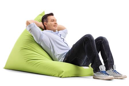 hombre sentado: chico joven relajado que pone en una bolsa de frijoles verdes cómoda aislado en el fondo blanco