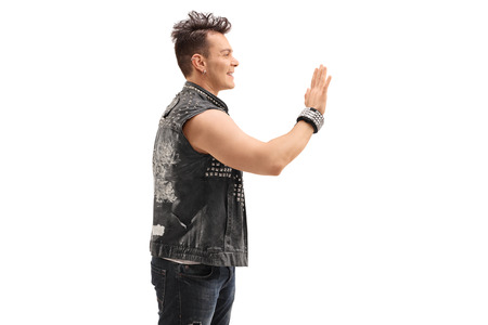 waving: Cheerful punk rocker waving to someone with his hand isolated on white background