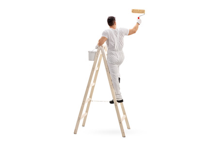 decorator: Young male decorator painting with a paint roller climbed up a ladder isolated on white background