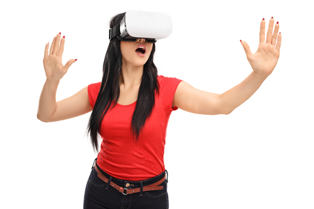 virtual reality simulator: Amazed girl experiencing virtual reality via VR goggles isolated on white background