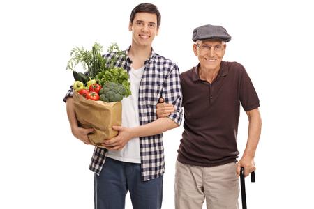식료품 가방을 들고 흰색 배경에 고립 된 그의 할아버지와 함께 포즈를 취하는 젊은 남자