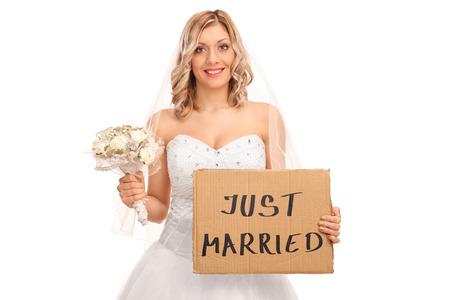 letreros: Novia alegre celebración de una boda con las flores y una bandera que apenas dice casado aislado en el fondo blanco