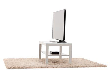 big screen tv: Studio shot of a big flat screen TV white table isolated on white background
