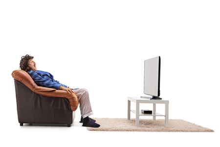ver tv: Hombre asustado viendo una película de terror en la televisión sentado en un sillón aislado en el fondo blanco Foto de archivo
