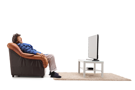 Scared man watching a horror movie on TV seated in an armchair isolated on white background Stock Photo - 59151445