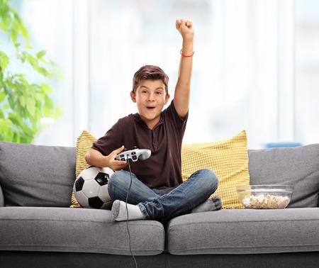 niño alegre que juega al videojuego de fútbol y celebrando un gol con el puño en el aire sentado en un sofá gris