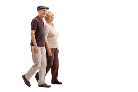 Mature couple walking together and smiling isolated on white background Foto de archivo