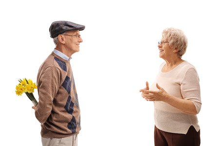 gift behind back: Senior man holding flowers behind his back on a date with an elderly woman isolated on white background