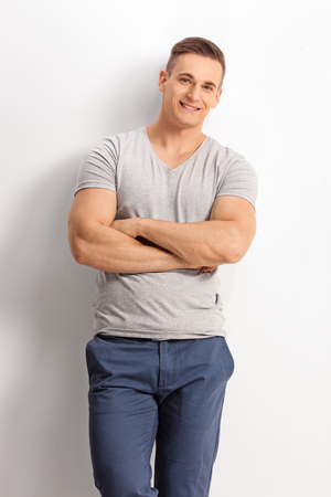 Vertical shot of a handsome casual man standing against a white wall and looking at the camera photo
