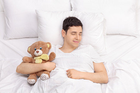 childish: Joyful childish guy sleeping peacefully with a teddy bear on a comfortable bed Stock Photo