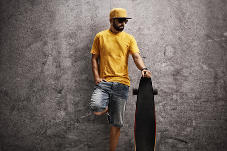 Cool man leaning against a rusty concrete wall and holding a longboard Stock Photo