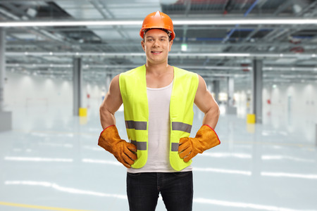 reflective vest: Cheerful male worker with an orange helmet and green reflective vest posing in a factory hall