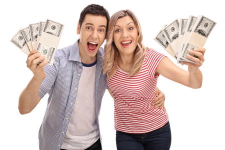 Joyful paar hand stapels geld en glimlachend geïsoleerd op een witte achtergrond