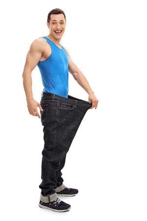 oversized: Full length portrait of a joyful guy in an oversized pair of jeans isolated on white background Stock Photo