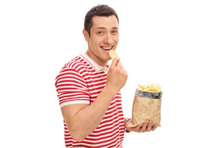 Junge fröhliche Kerl Kartoffelchips essen und in die Kamera schaut auf weißem Hintergrund