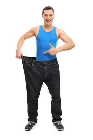 oversized: Full length portrait of a handsome man showing his old pair of oversized jeans isolated on white background