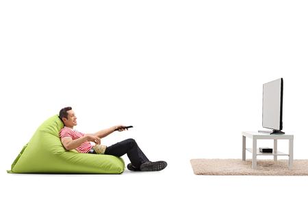relajado hombre sentado en una bolsa de frijoles verdes cómoda y viendo la televisión aislado en el fondo blanco