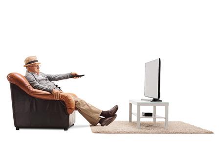退屈シニア アームチェアに孤立した白地の上に座って彼のテレビのチャンネルを変更します。
