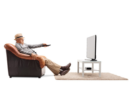 changing channels: Bored senior changing channels on his TV seated on an armchair isolated on white background