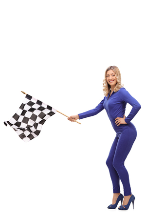 racer flag: Vertical shot of an attractive woman in a one-piece racing suit waving a checkered race flag isolated on white background
