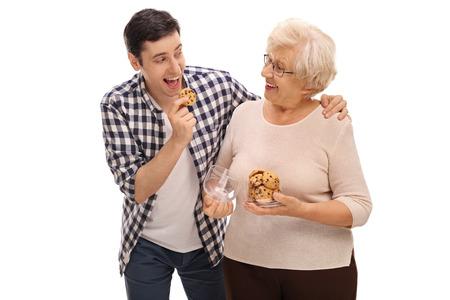 Ältere Dame, selbst gebackenen Plätzchen zu einem jungen Mann auf weißem Hintergrund geben