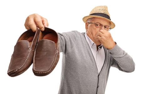 白い背景で隔離の臭い靴のペアを保持うんざりシニア 写真素材