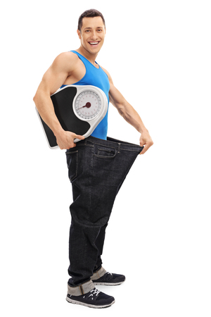 oversized: Full length portrait of a handsome guy in an oversized pair of jeans holding a weight scale isolated on white background Stock Photo