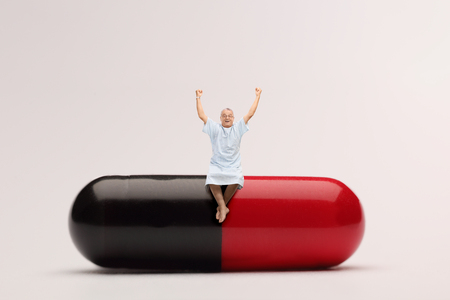 capsule: Cheerful mature patient sitting on a giant pill and gesturing happiness Stock Photo